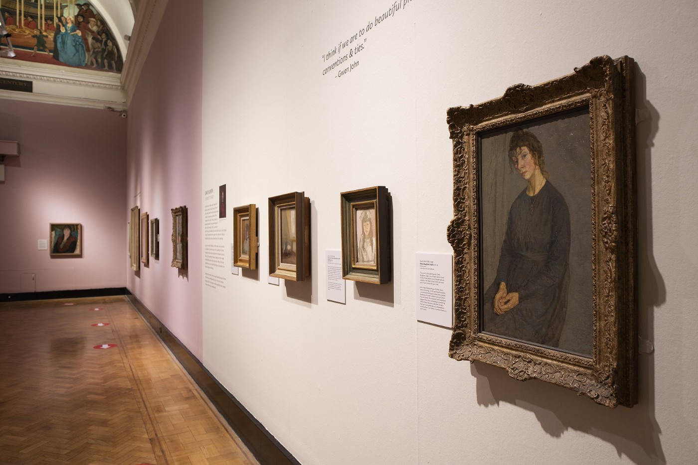A photo of a gallery wall with gold frames hung on it, with a painting of a sitting woman wearing a black dress
