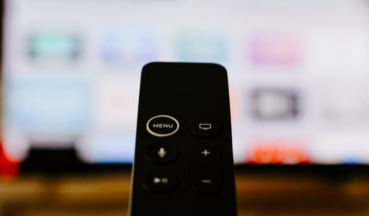 Apple tv remote control in front of the Apple tv.