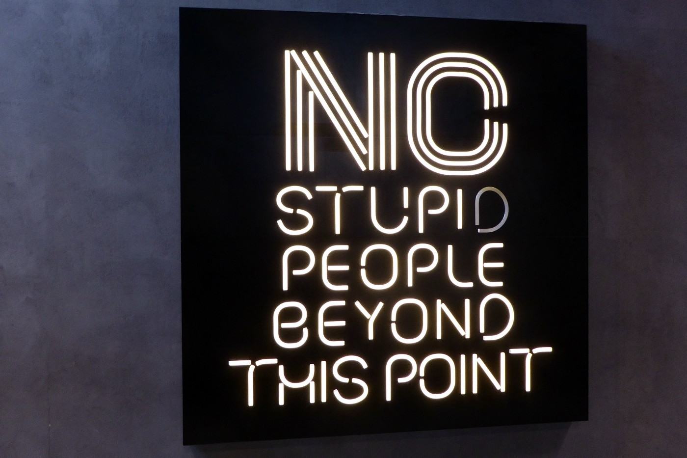 Black sign with neon writing on it