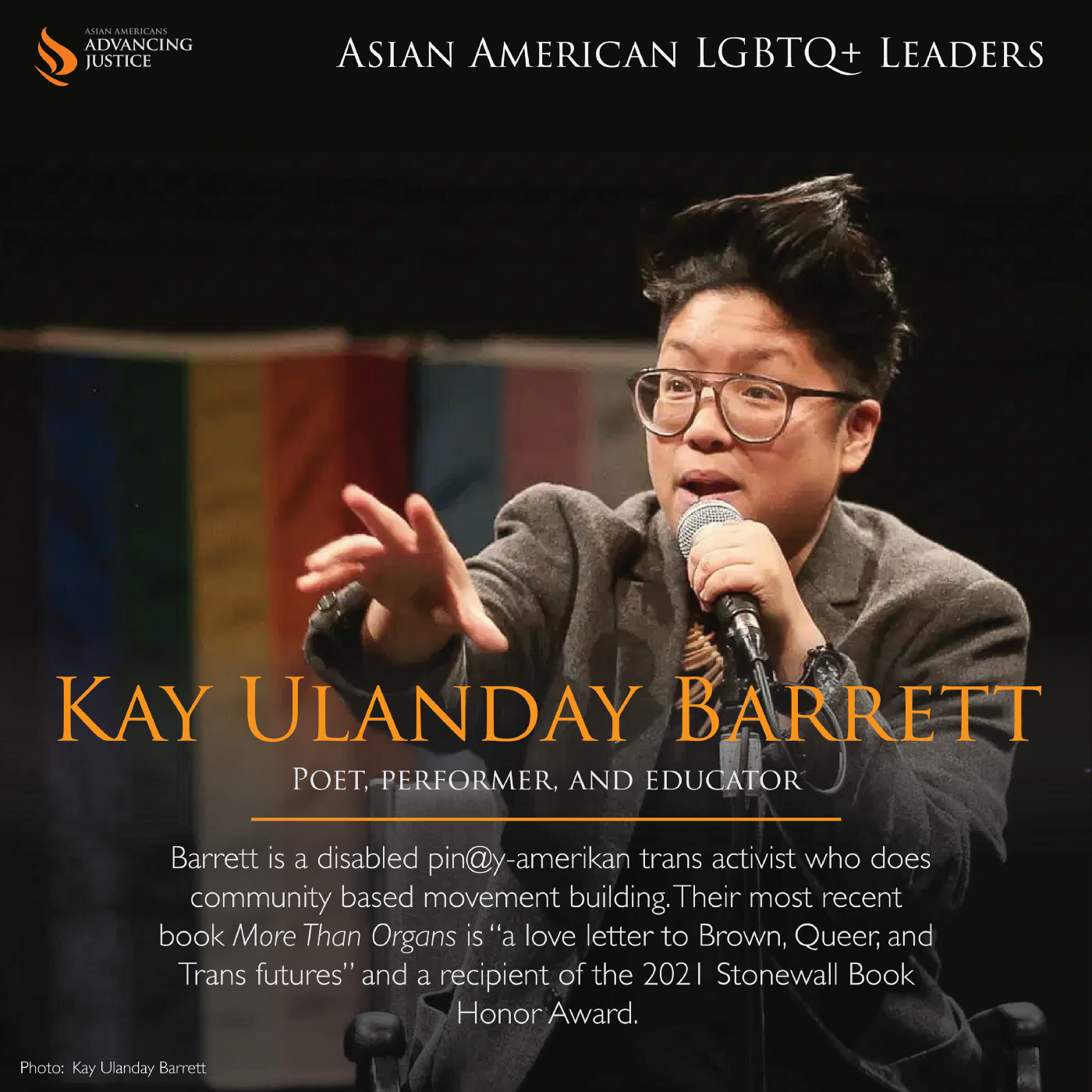 """Barrett in a grey suit coat, holding a microphone in one hand and gesturing with the other in front of a rainbow gay pride and blue, pink, and white transgender pride flag. The text reads: Kay Ulanday Barrett, Poet, performer, and educator. Barrett is a disabled pin@y-amerikan trans activist who does community based movement building. Their most recent book More Than Organs is """"a love letter to Brown, Queer, and Trans futures"""" and a recipient of the 2021 Stonewall Book Honor Award."""