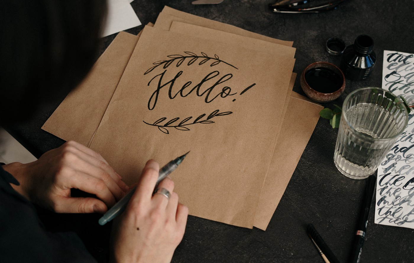 """The word """"Hello"""" written in calligraphy on a cardstock."""