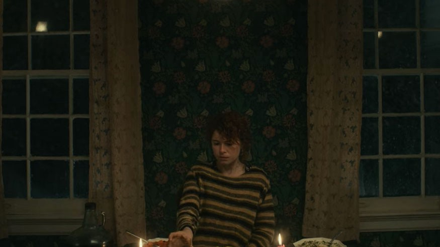 """The young woman, who is the main character of the movie """"i'm thinking of ending things,"""" is putting a cup down on the dining table, which is full with food."""