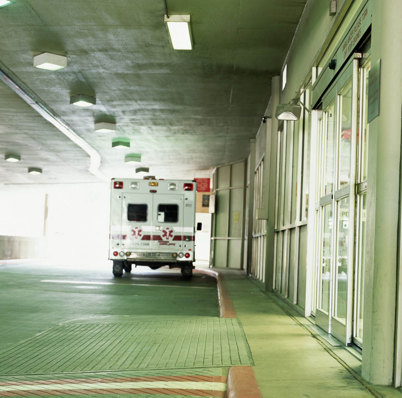 A photo of an ambulance in front of a hospital entrance.