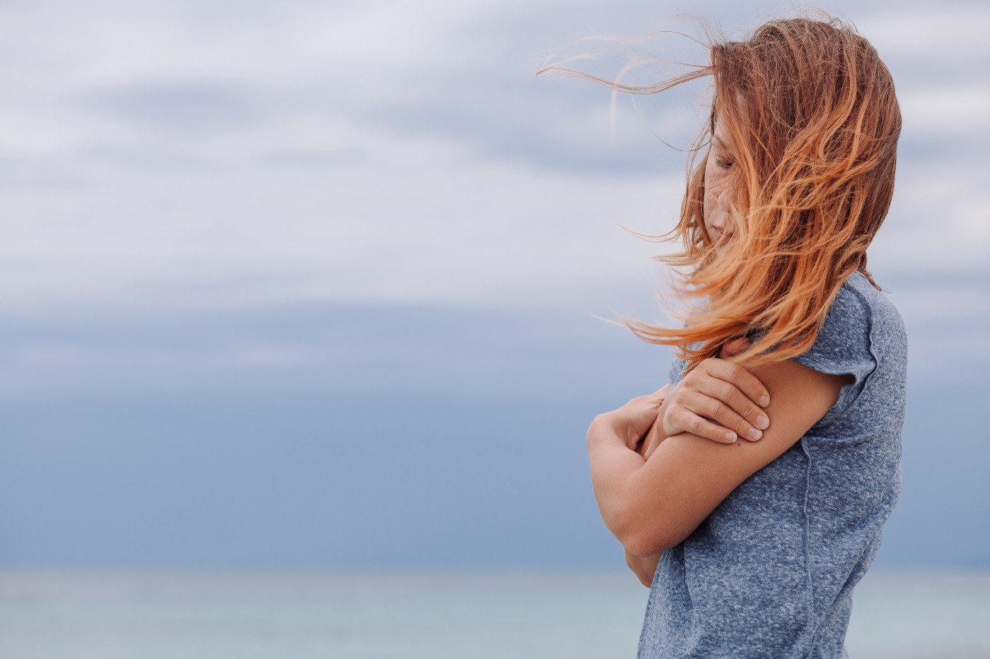 Sad woman in a dusty blue shirt with auburn hair covering most of her face, arms crossed, on the beach on a blustery day