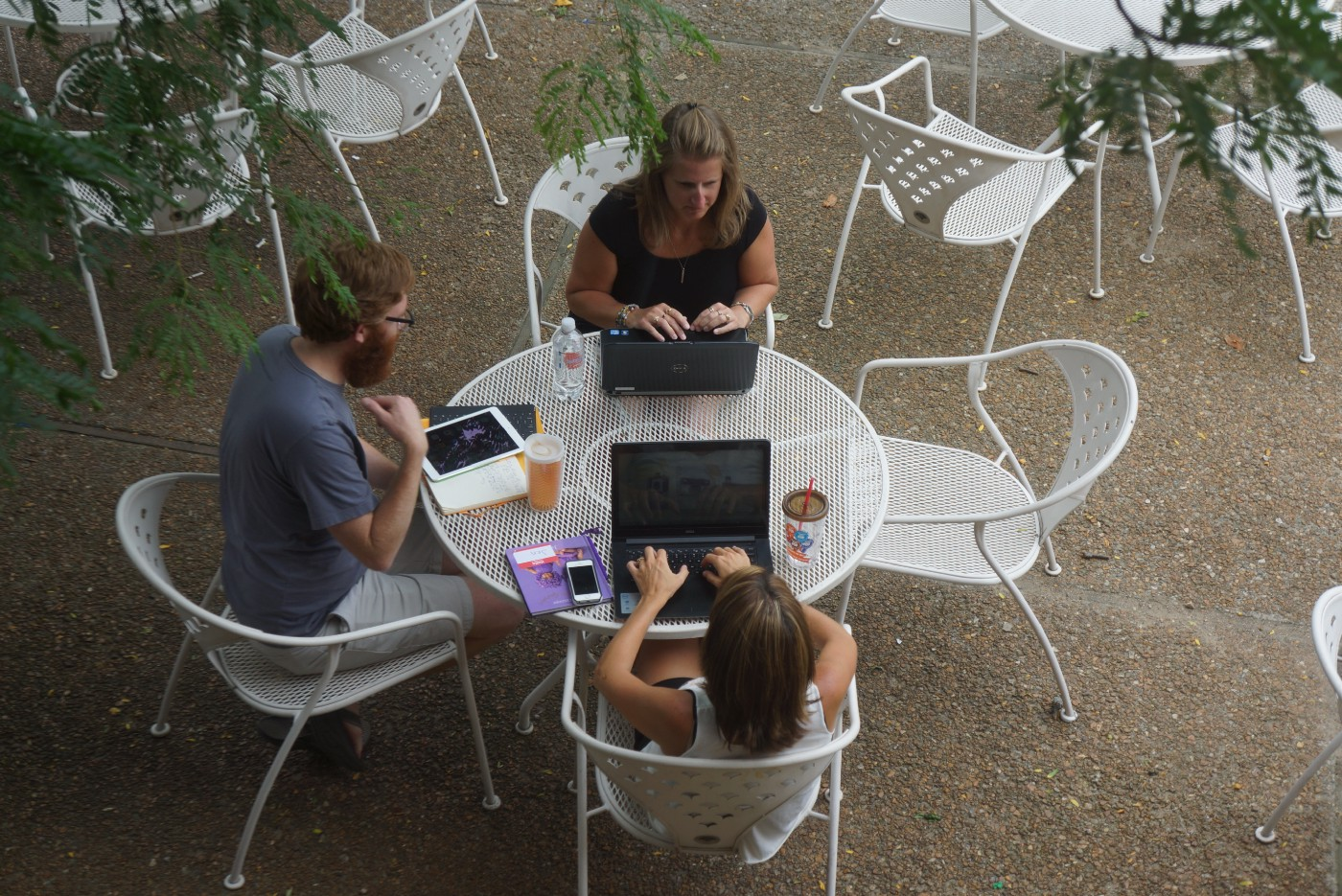 A man and two women sitting around an outdoor table, talking. On the table are books, computers, and writing materials.