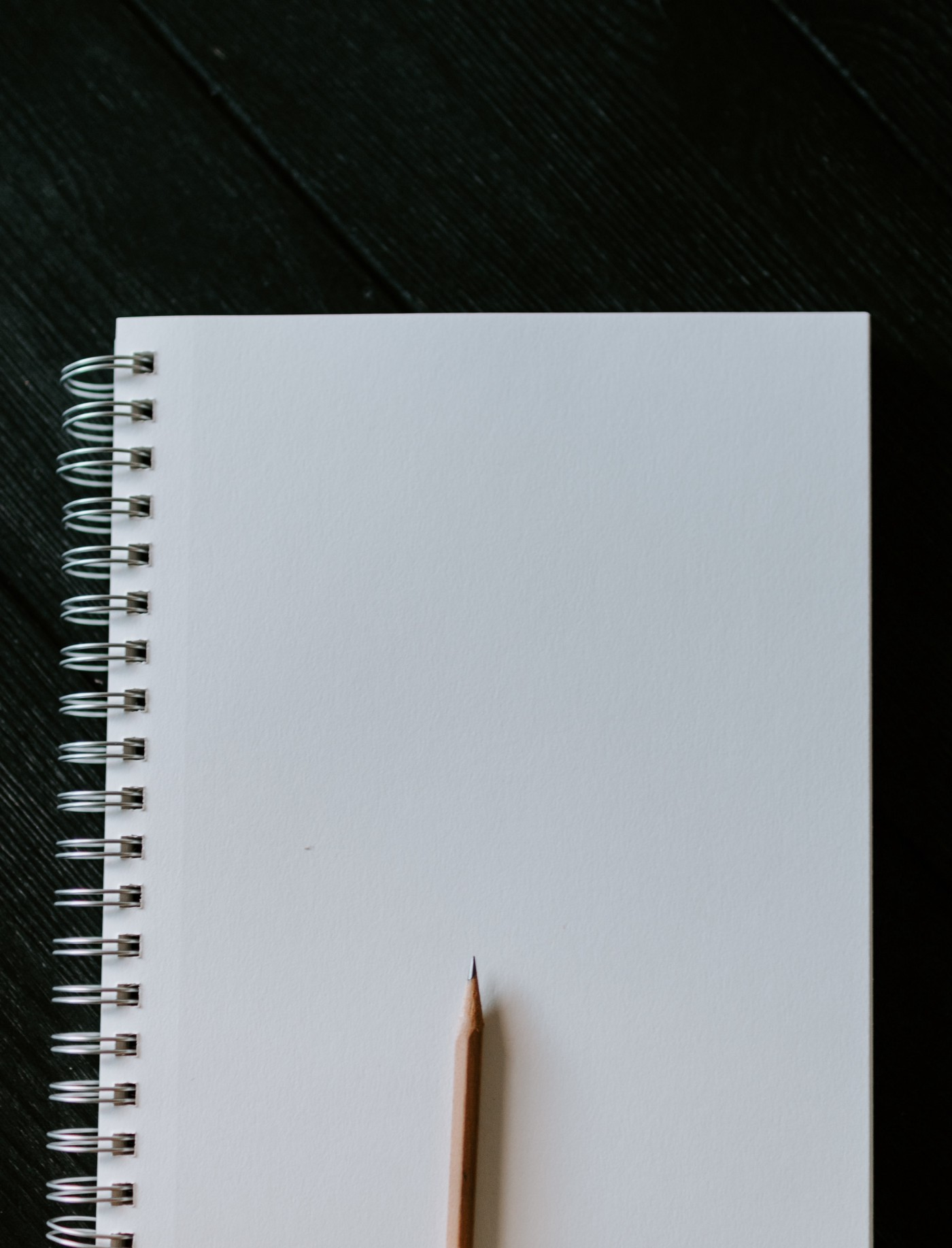 Black background, fresh white page of spiral bound notebook, and a freshly sharpened pencil