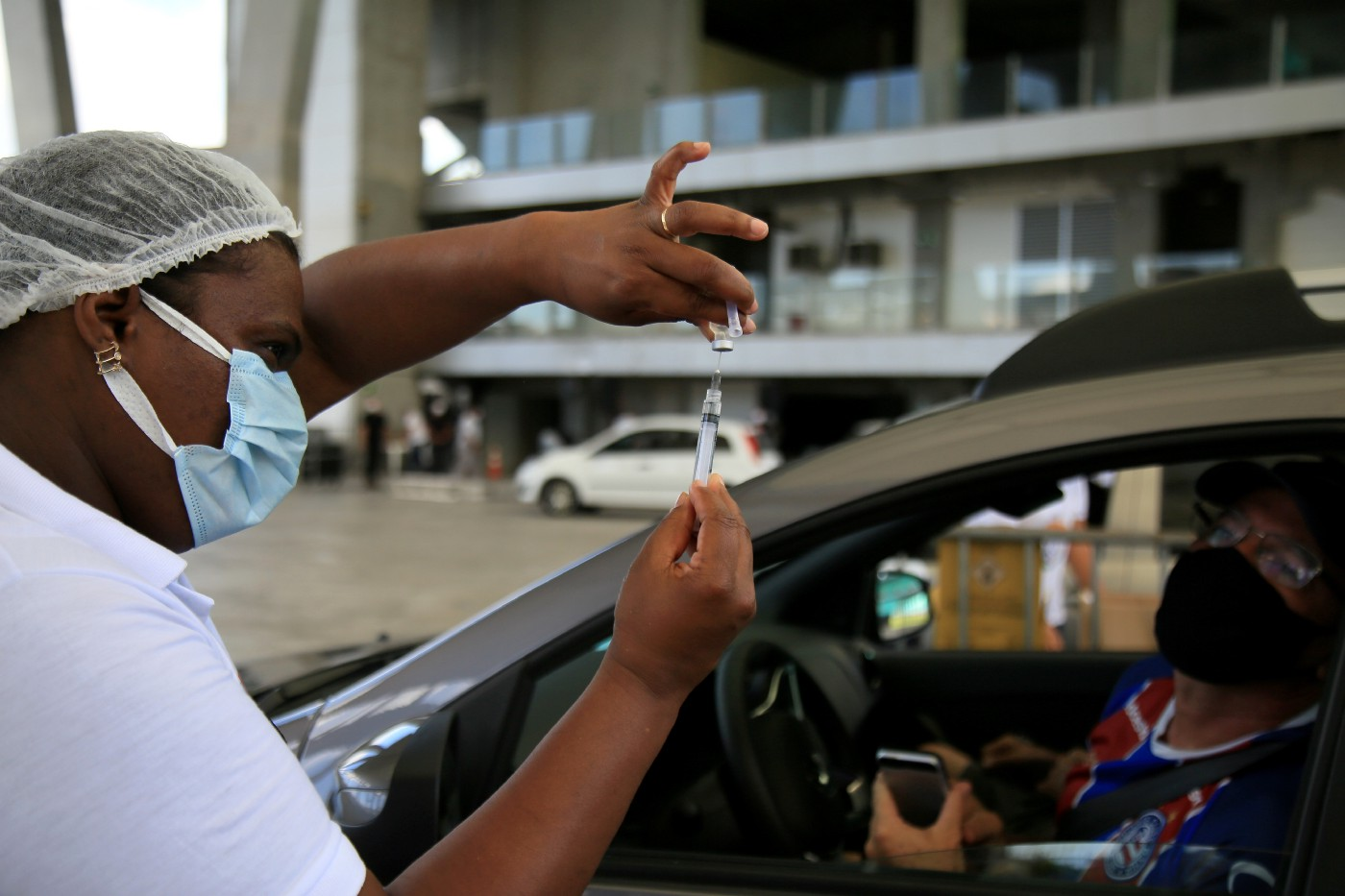 A health worker in a surgical mask prepares a syringe of Covid-19 vaccine. The patient waits in their car with the window rolled down. State of Bahía, Brazil. February 2021.