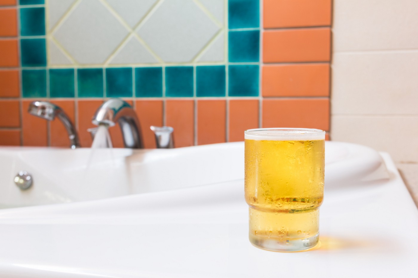A glass of beer placed on a surface near a running tap.