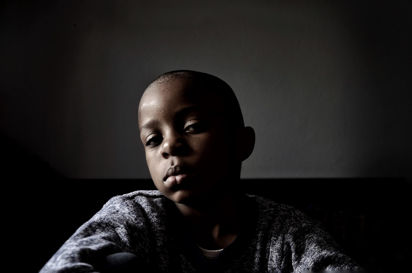 Shadowy portrait of a Black child with shaved hair.
