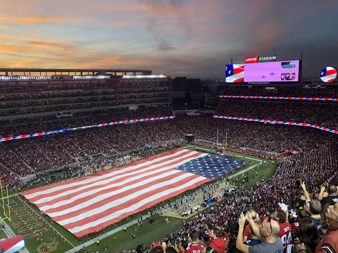 A packed Levi's Stadium (Santa Clara, California) with a massive American flag rolled out onto the field. The sun is setting and there are some clouds in the sky. Fans are taking pictures with their smartphones and cheering loudly.