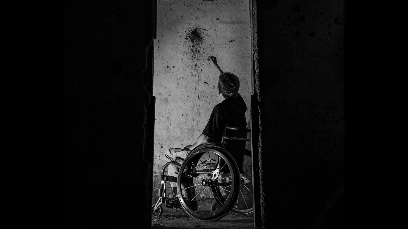 Black and white picture of many in wheelchair reaching out to splatter on the wall.