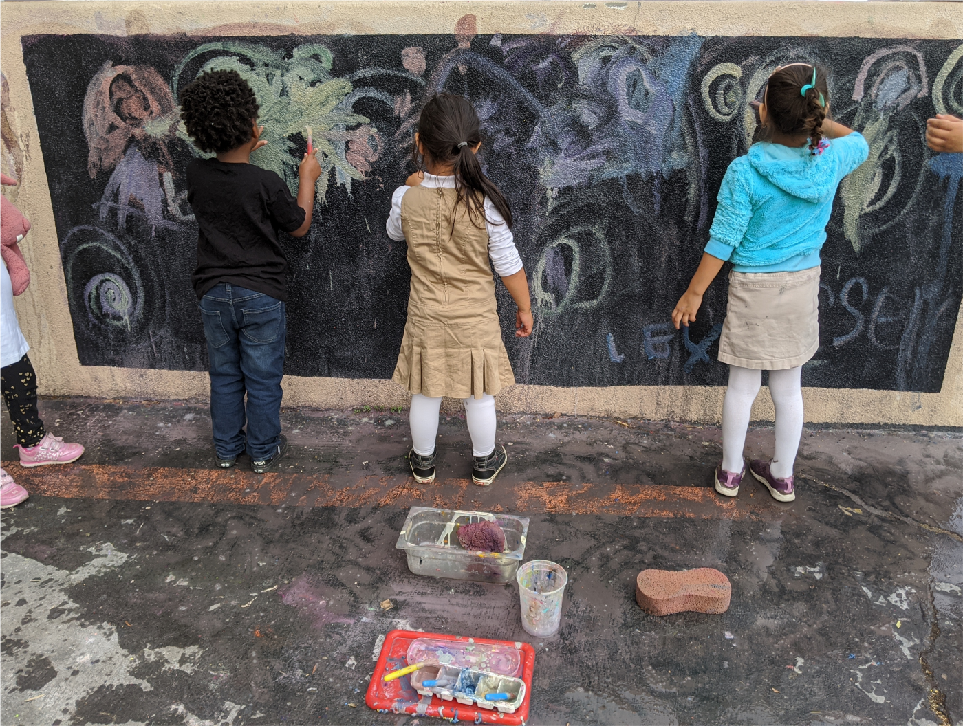 Three children painting on an outdoor chalkboard with chalk paint.