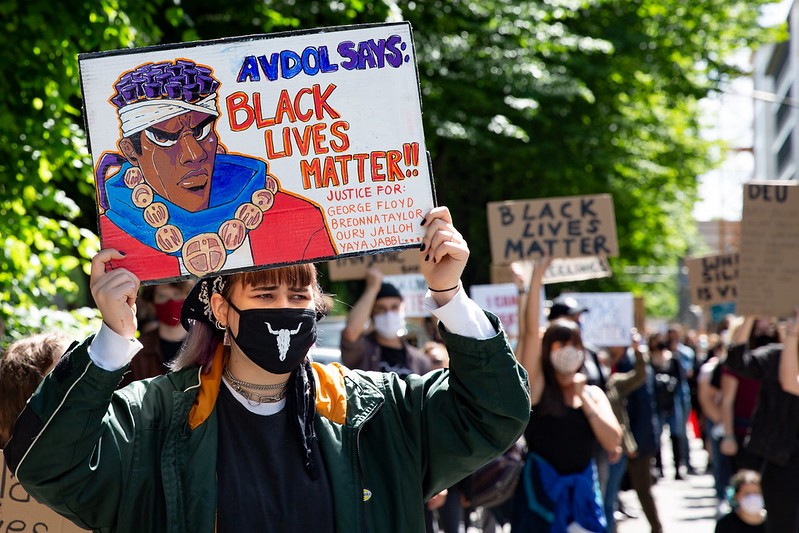 """A white woman at a march holds up a sign with a Black comic character that reads, """"Avdol Says: Black Lives Matter!"""""""