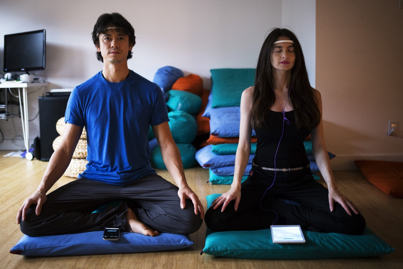 Chris Aimone and Ariel Garten, cofounders of InteraXon, are sitting down in seated positions wearing the Muse headband.