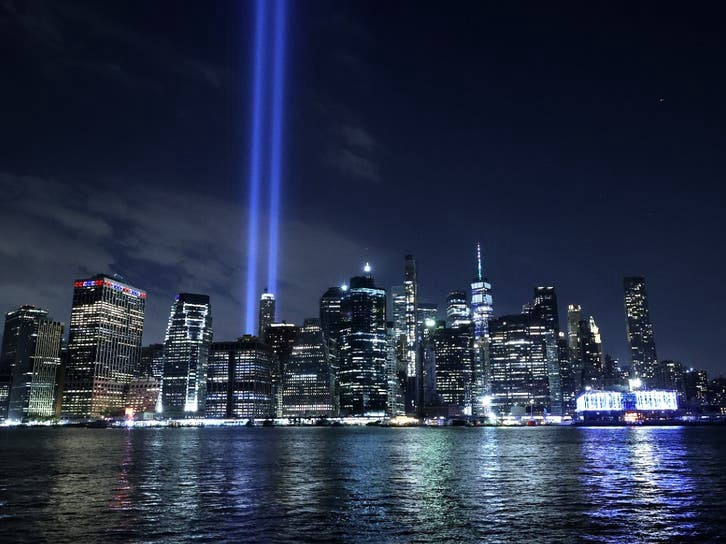 Two light beams reach into the night sky in front of New York Bay, representing the space where the World Trade Center twin towers once stood.