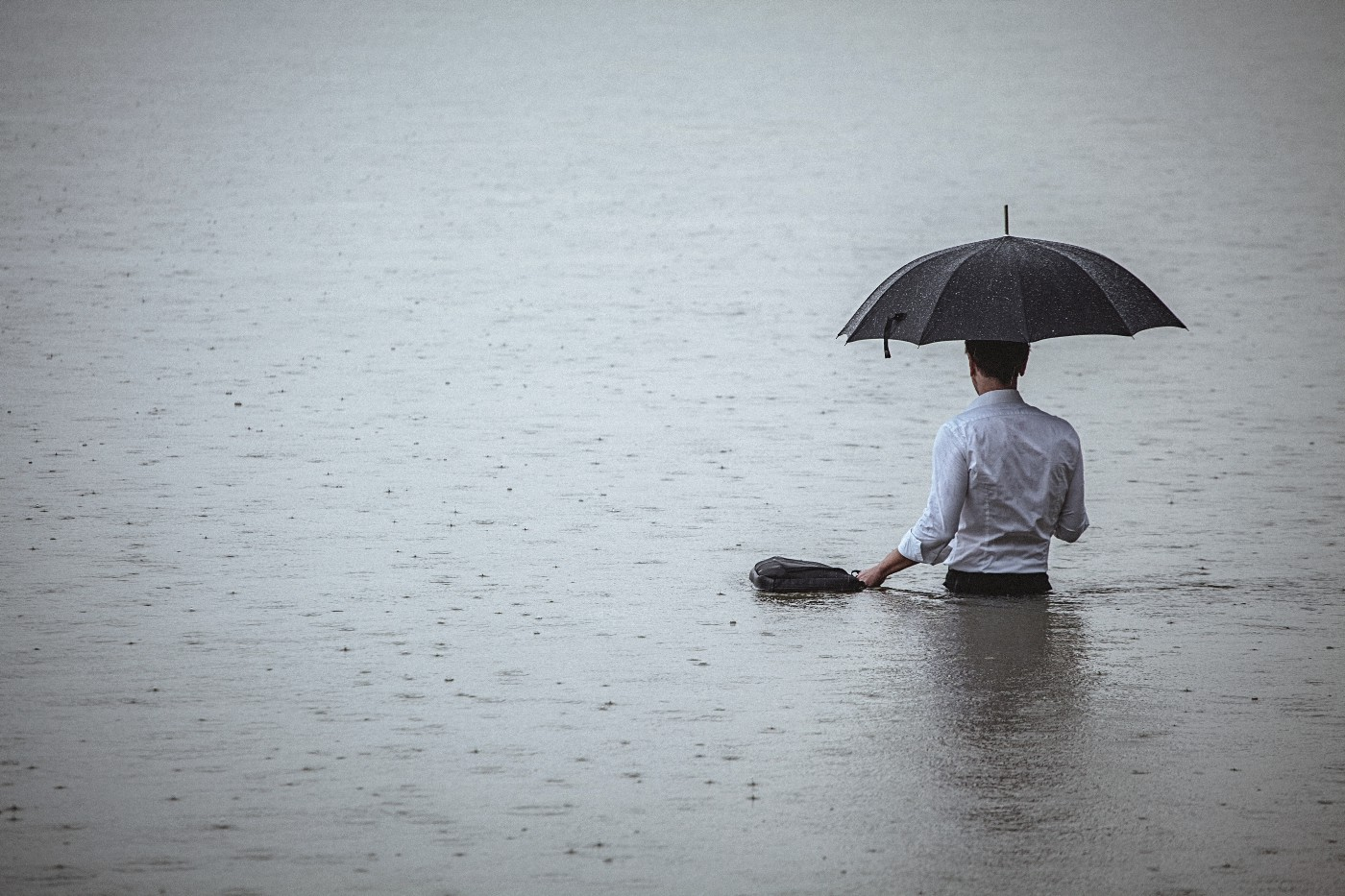 A man wearing a white shirt, holding up an umbrella and a briefcase, standing waist-deep in the water on a rainy day.