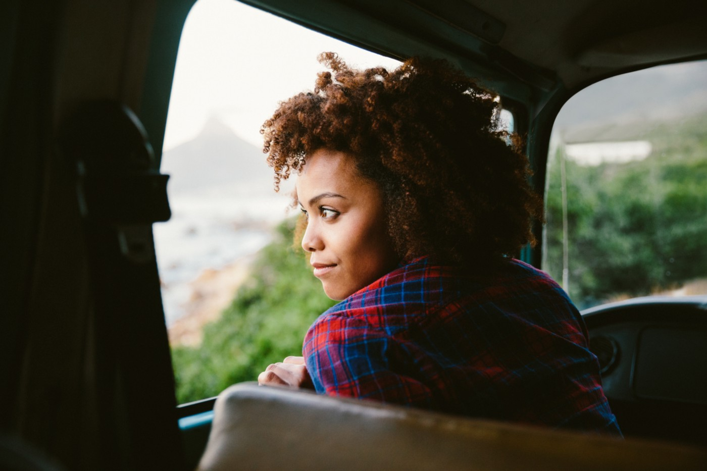 Black woman looking out the window of her car from the driver seat.