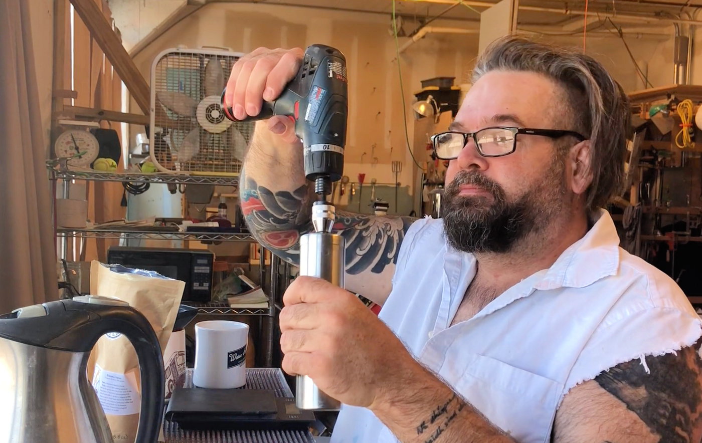Guy using a drill to grind coffee.