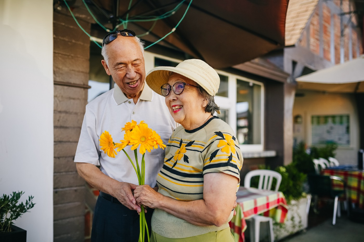 Two seniors, one is holding yellow flowers and the other one is looking at them.
