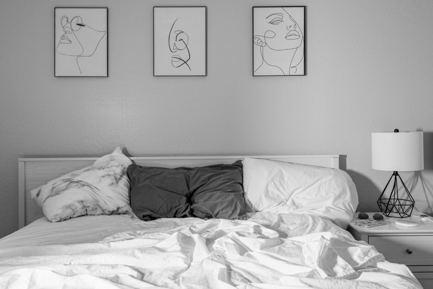Rumpled cotton sheets on a queen sized bed with three different pillows at the head. Monochrome palette, gray and white.