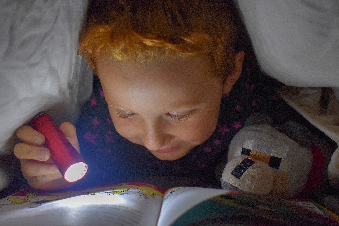 Child reading with a flashlight