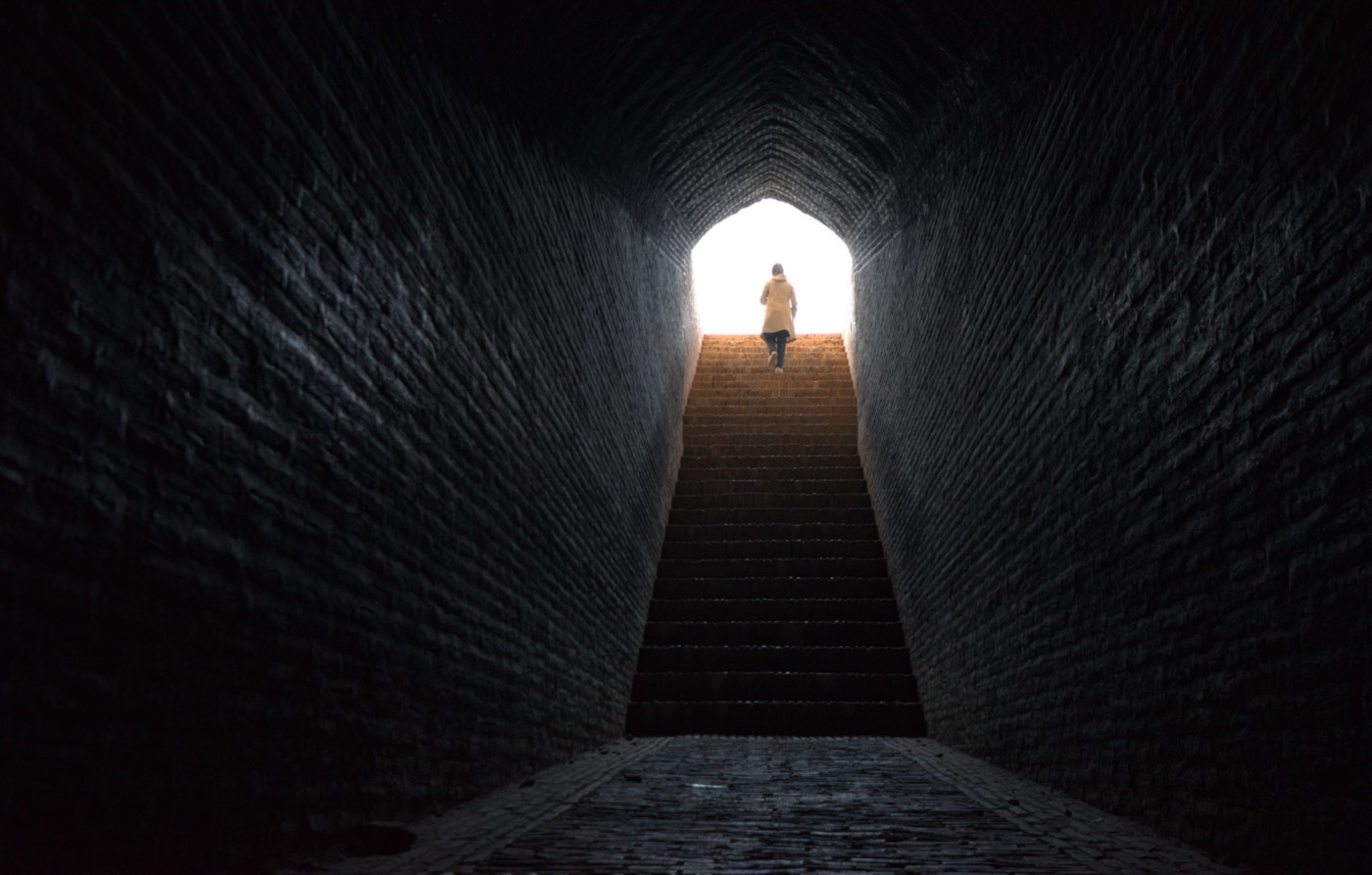A lone woman walks with confidence up stairs coming out from dark tunnel into bright light.