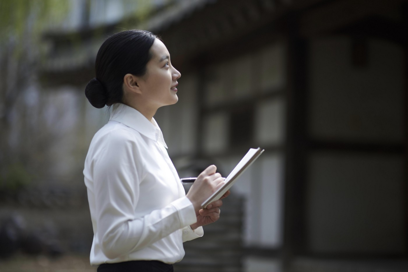 Asian businesswoman taking notes outside while looking at a building.