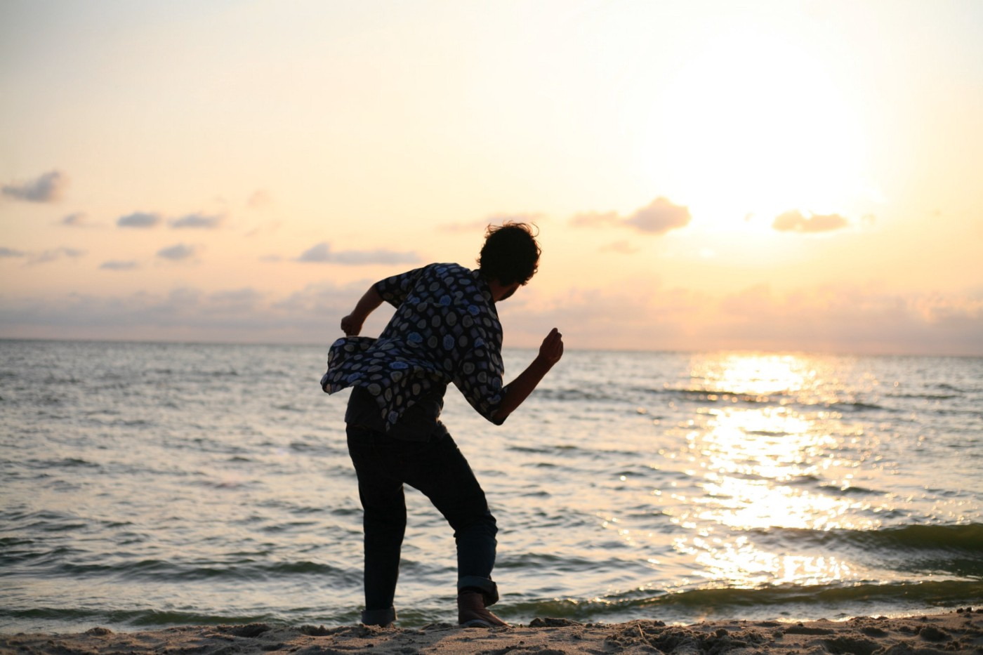 A young child skimming stones at the beach