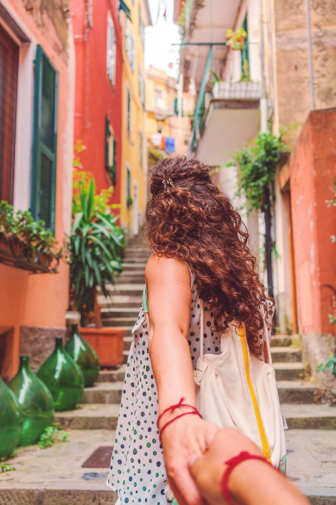 Woman in colorful alleyway, reaching back to hold the hand of the photographer