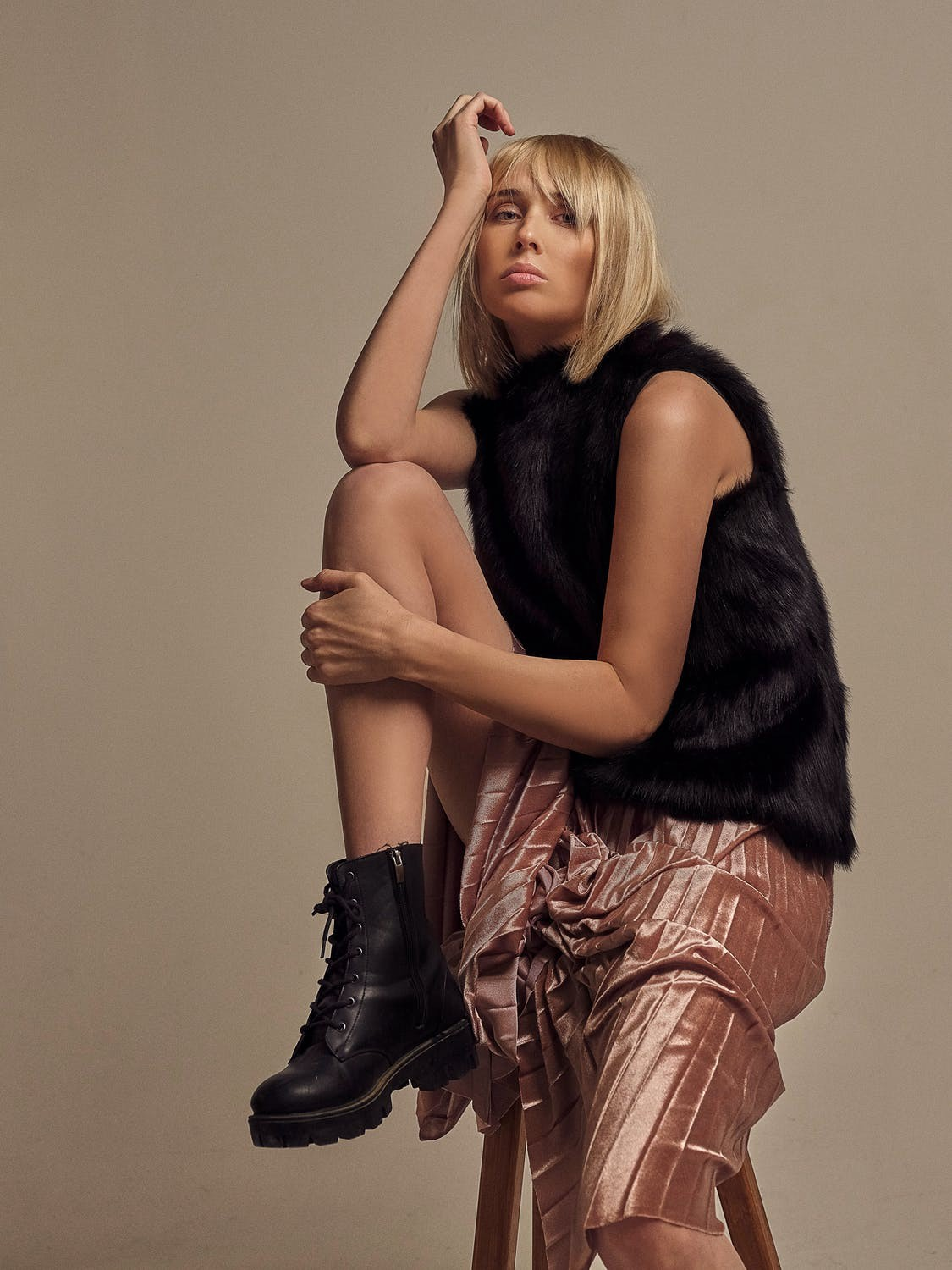 A model wearing a furry black top, glossy skirt, and a pair of black ankle boots