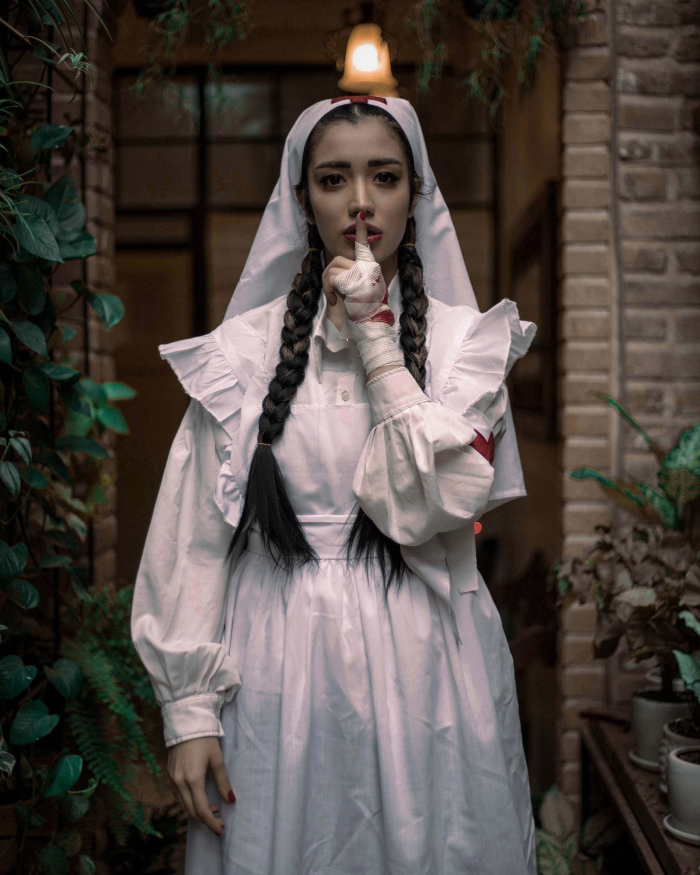 A woman in a nurse costume with two long braids in her hair presses her fingers to her lips, somewhat provocatively
