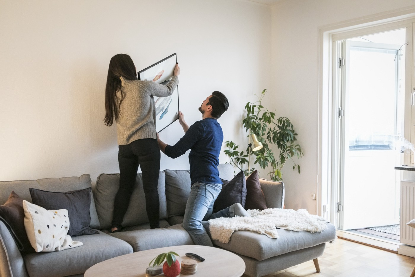 A couple hanging a framed picture on their living room wall.