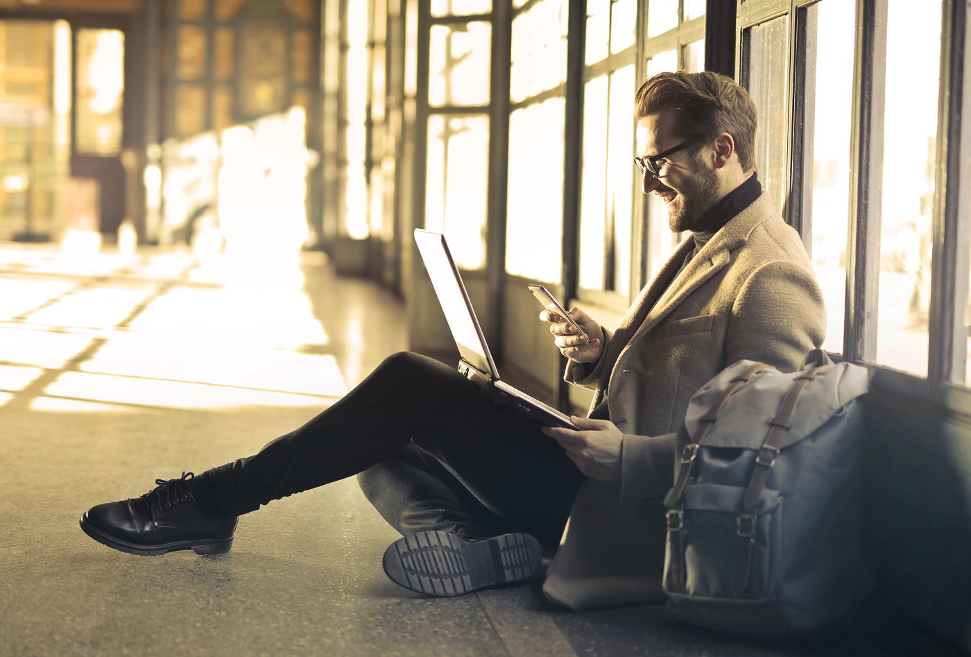 Business traveller sitting on ground with laptop