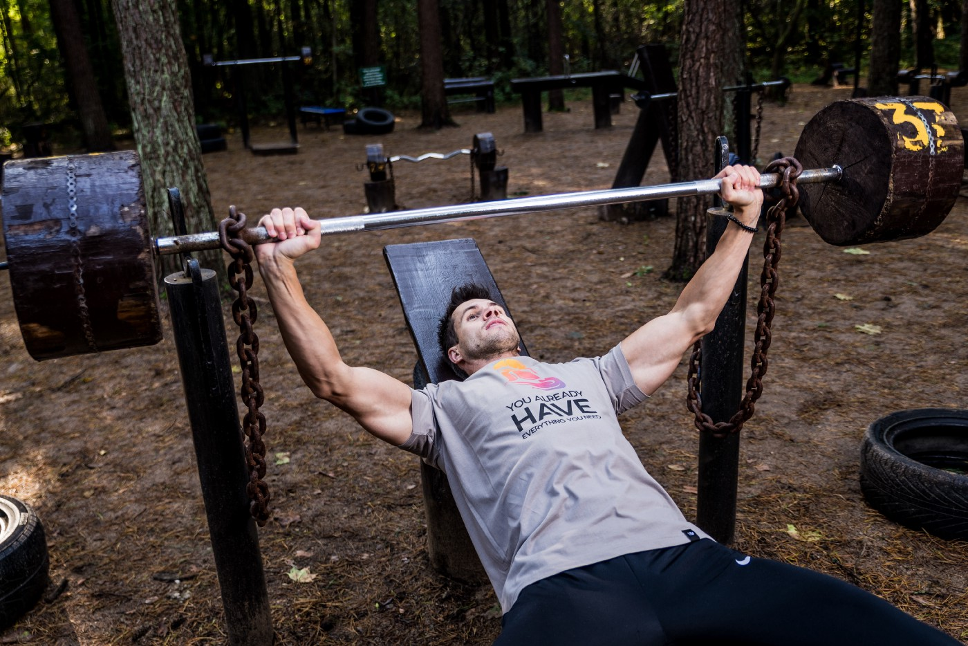 man on an incline bench press in a shared outdoor gym