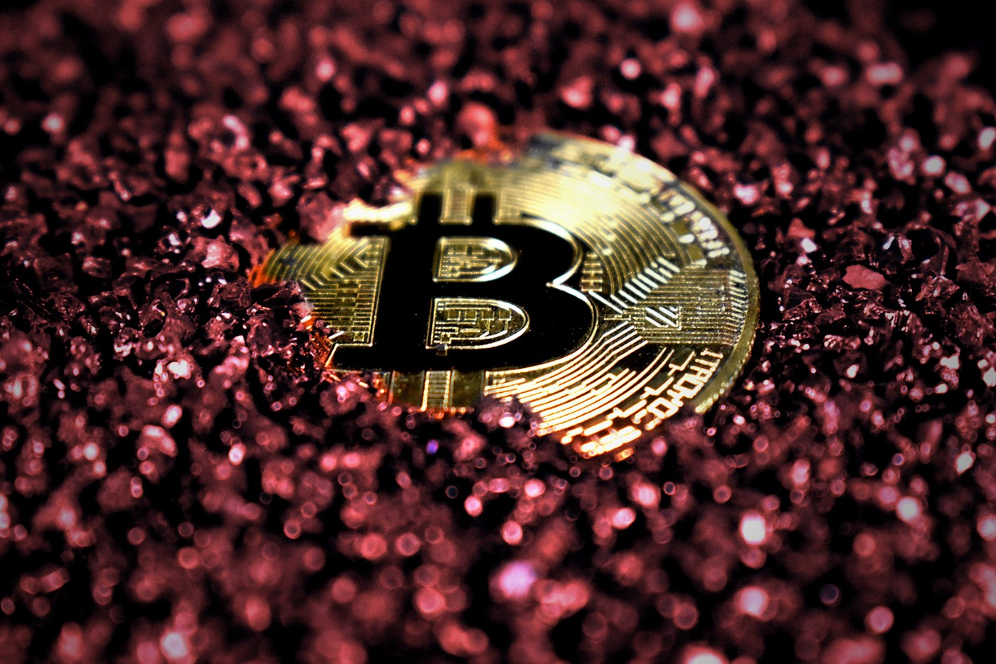 A gold 'bitcoin' in red glitter.