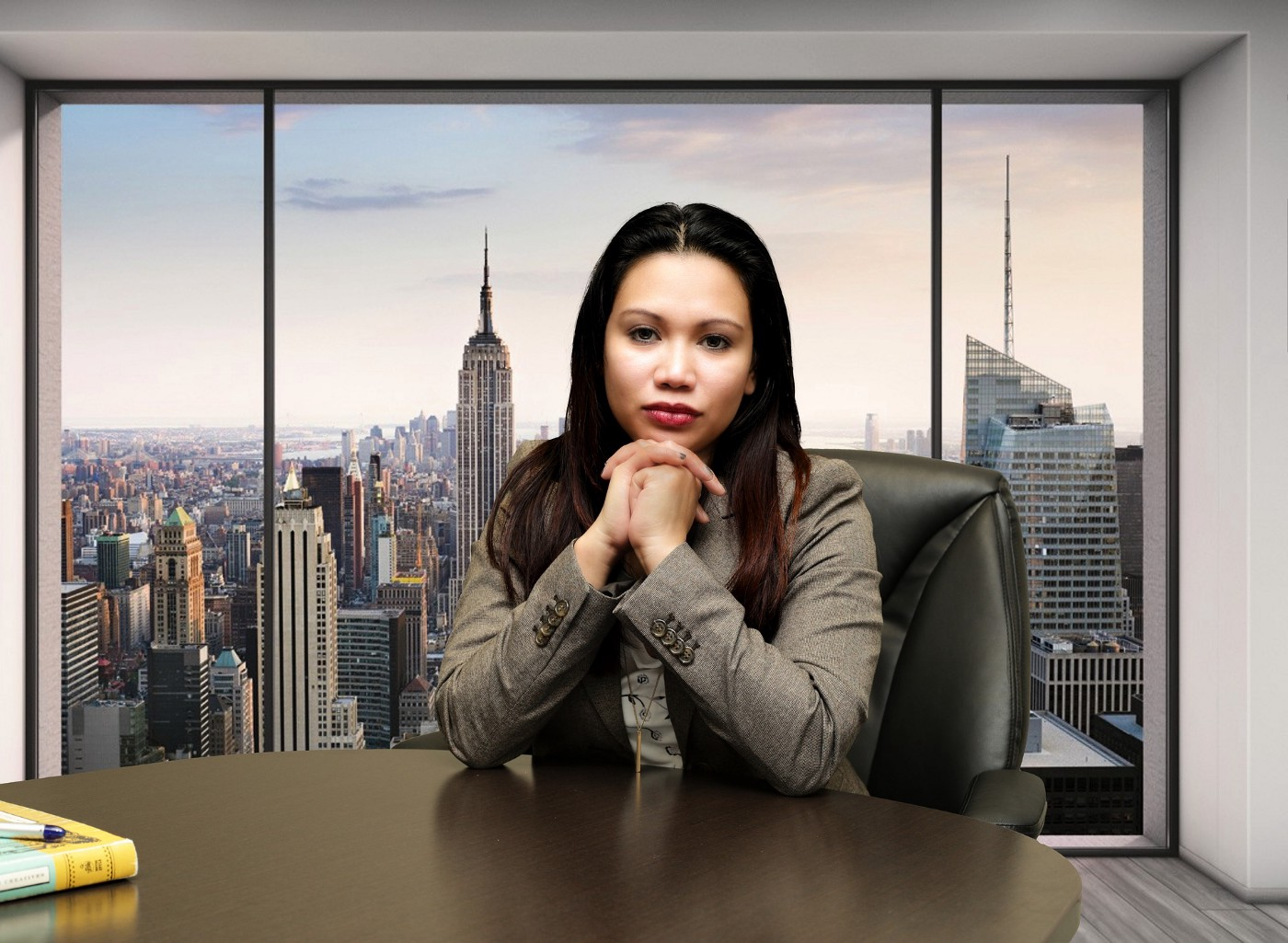 Asian woman professional sitting with her hand on the table. Behind her there is city skyline visible through glass window.