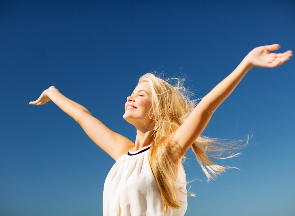 A happy and smiling woman cleansing her mind by releasing her toxins to the nature.