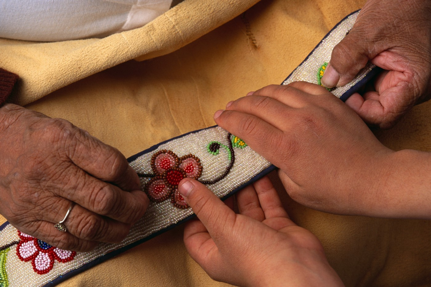 A photo of an elderly Ojibwe showing an embroidery to a young child.