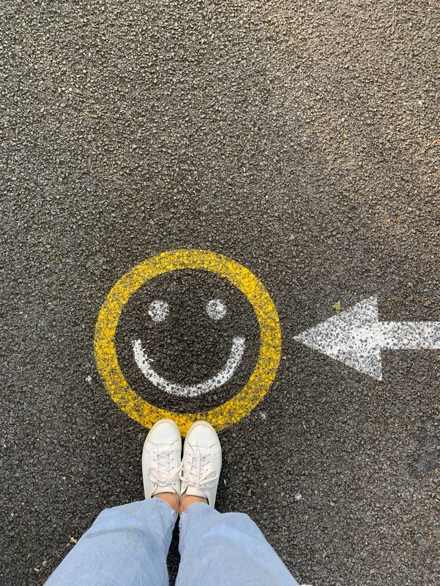 A person's feet in front of a smiling emoji