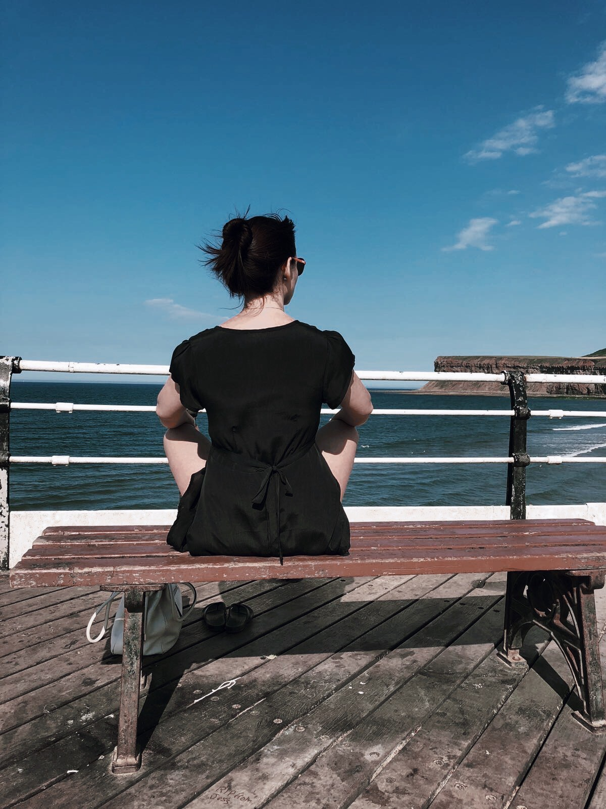 Back view of lady sitting crosslegged on a bench looking out to sea