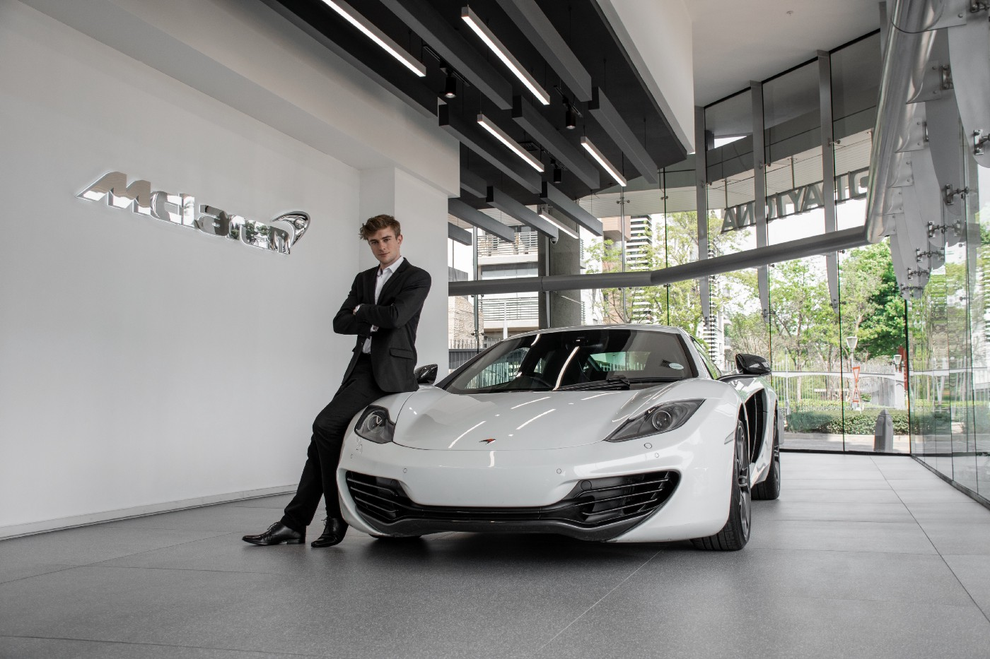A man in a suit with a white McLaren sports car. He is young and has dark blonde hair. His arms are crossed in front of his body and he is leaning on the passenger side of the fancy sports car.