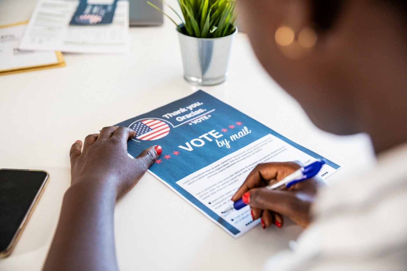 Young Black woman filling out a paper ballot to vote by mail.