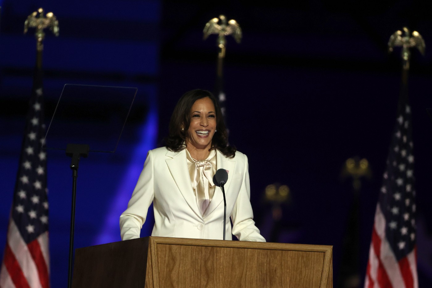 Vice President-elect Kamala Harris wearing a white suit giving an address to a crowd in Wilmington.