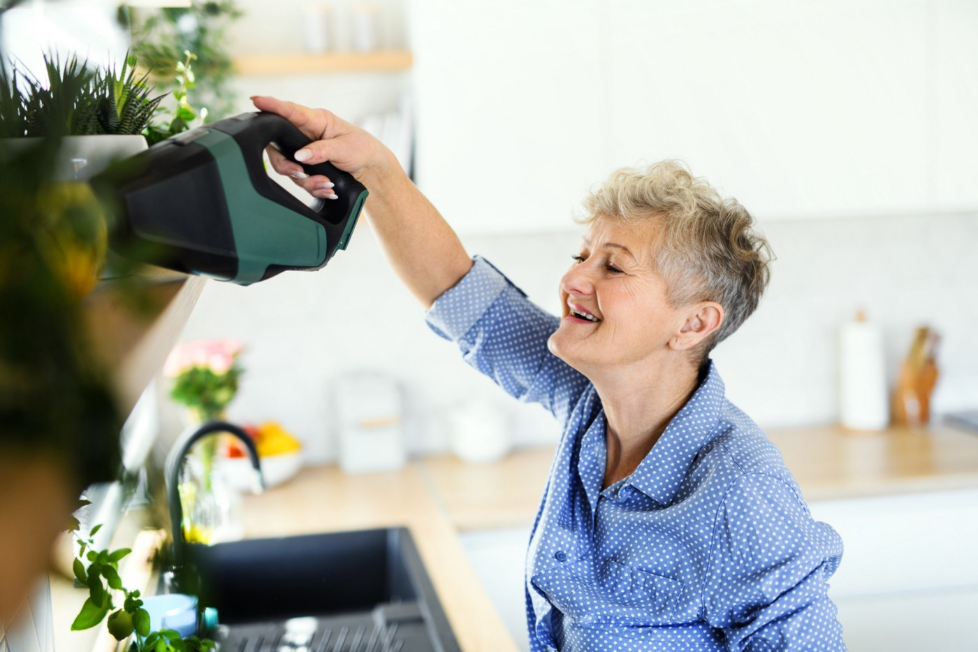 Woman cleaning her kitchen with a smile.