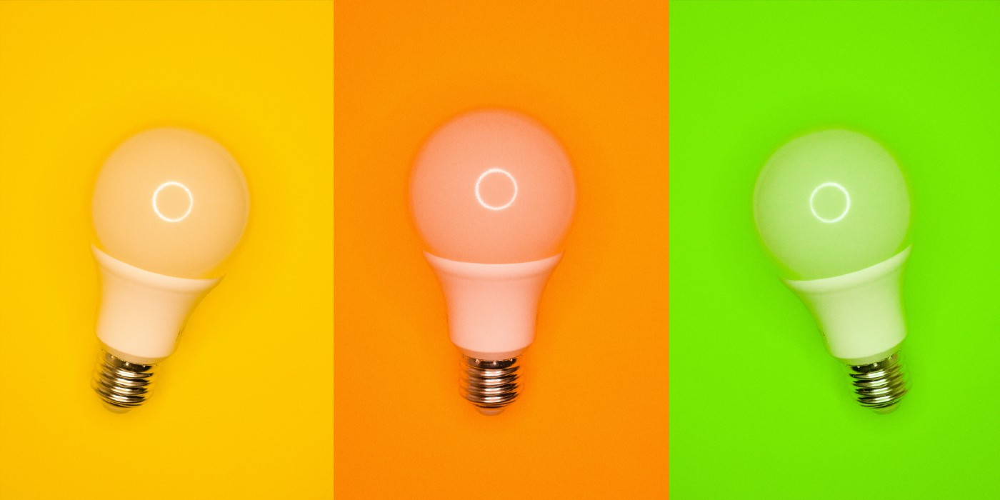 Three light bulbs side by side and divided into three rectangles with yellow, orange, and green backgrounds