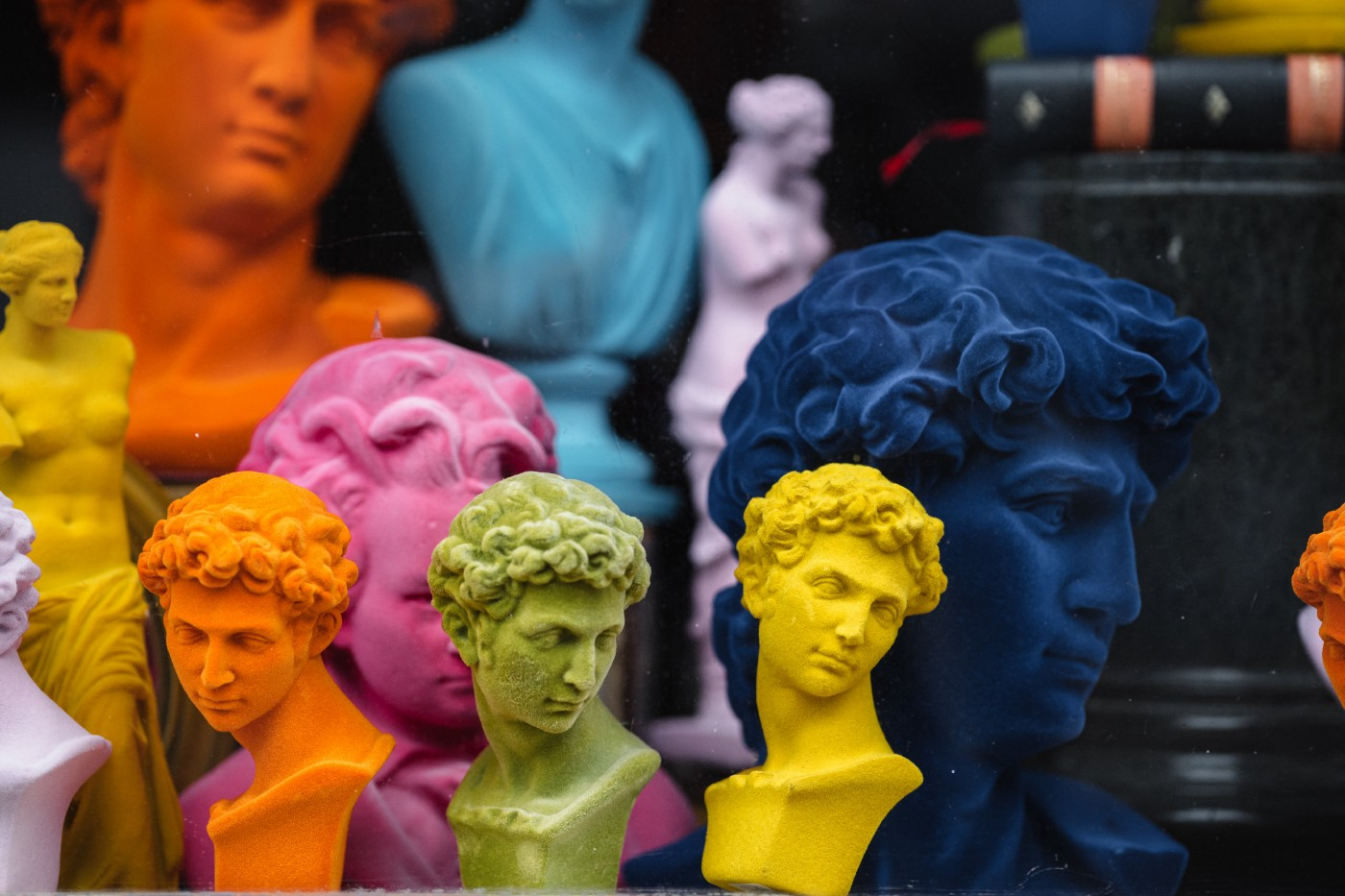Plaster heads of Greek philosophers painted in different sizes and colors to. buy at a souvenir shop—orange, yellow, green, pink