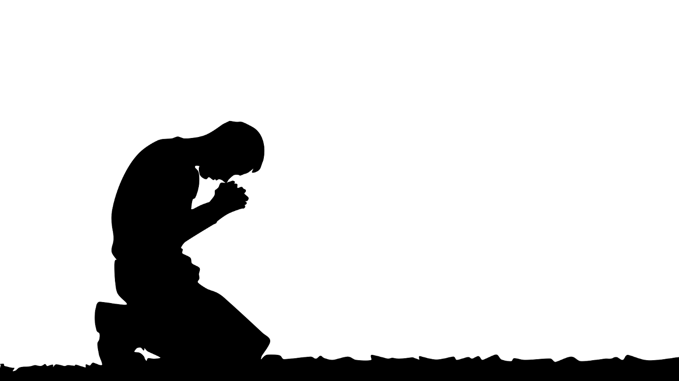 silhouette of a man kneeling and praying
