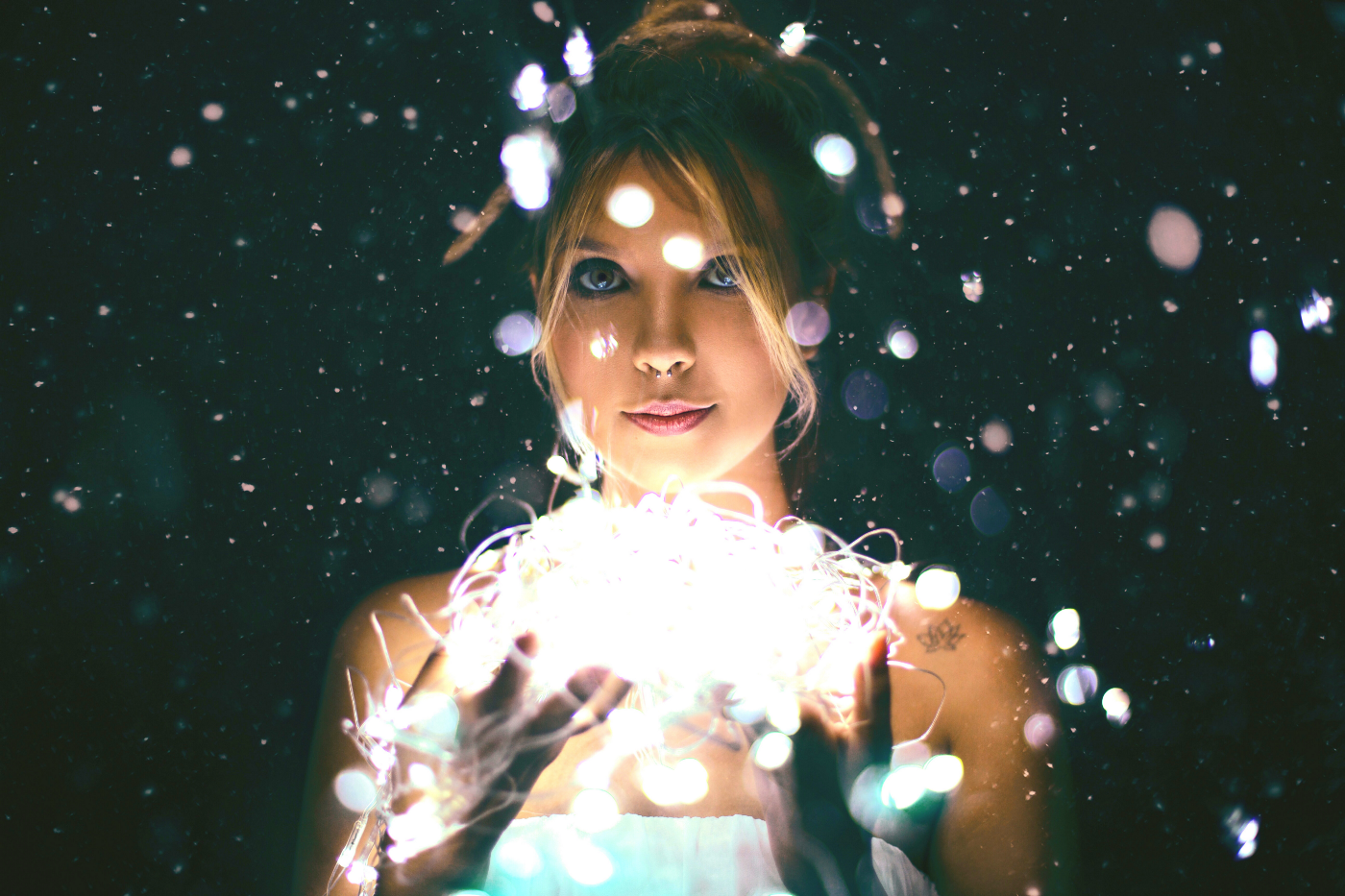 A woman in the dark holds fairy lights in both hands.