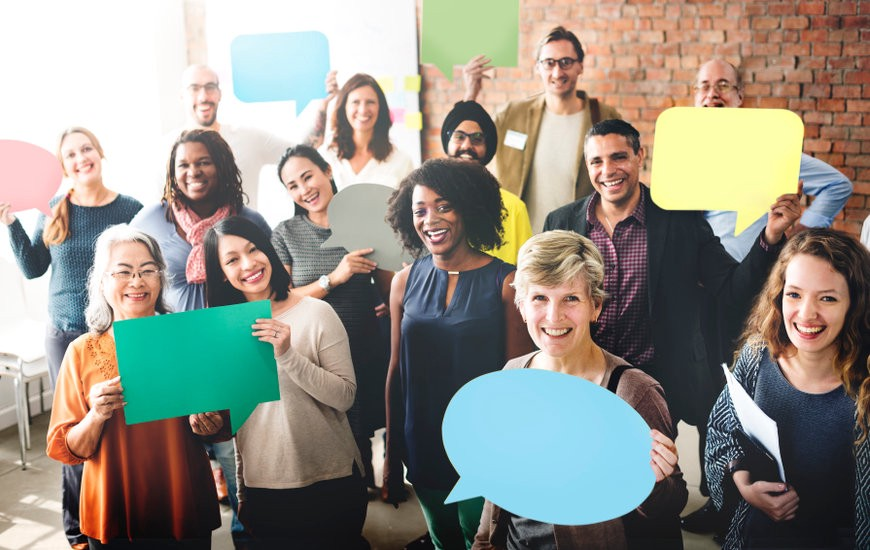 A group of smiling diverse co-workers, some holding up large colorful speech bubbles.