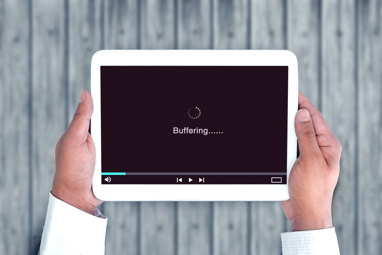 An above shot of unrecognizable hands holding a tablet with a buffering website due to poor user experience.